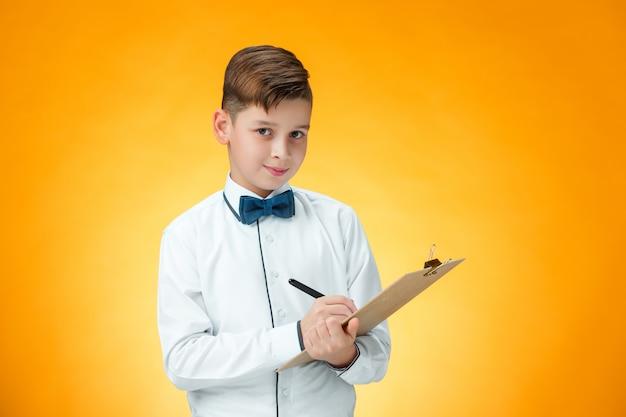 El niño con bolígrafo y tableta para notas Foto gratis