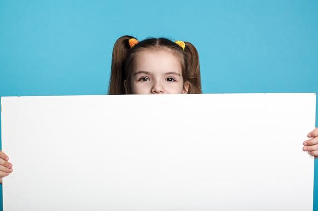 Niño de cabello oscuro con tablero blanco Foto Premium
