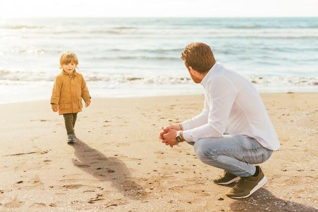 Niño caminando en la playa con papá Foto gratis