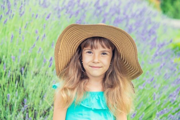 Un niño en un campo de flores de lavanda. enfoque selectivo Foto Premium