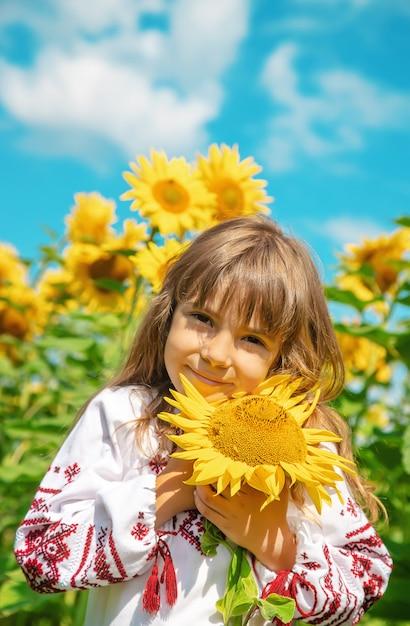 Un niño en un campo de girasoles con una camisa bordada. Foto Premium