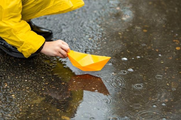 Niño con capa impermeable amarilla y botas de goma negras jugando con papel barco de juguete hecho a mano en un charco al aire libre bajo la lluvia en otoño. Foto Premium