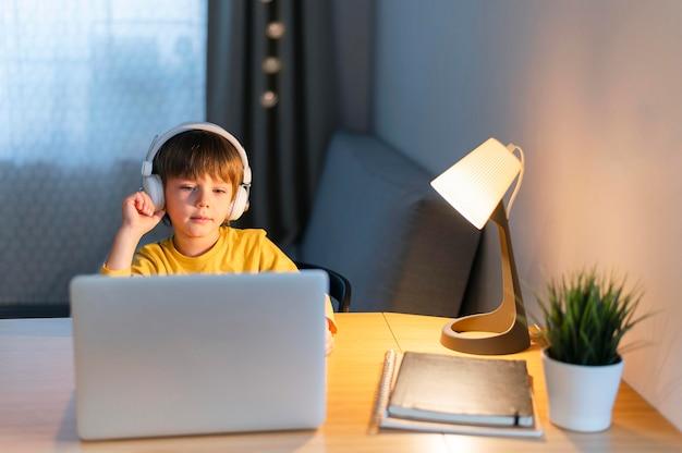 Niño en casa tomando cursos virtuales Foto gratis