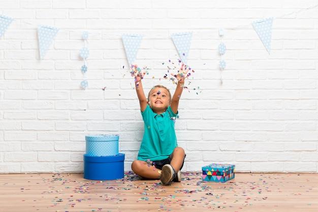 Niño celebrando su cumpleaños con confeti en una fiesta Foto Premium