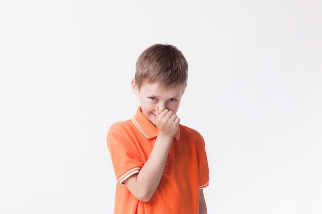Niño cerrando la nariz con los dedos mirando a la cámara sobre fondo blanco. Foto gratis
