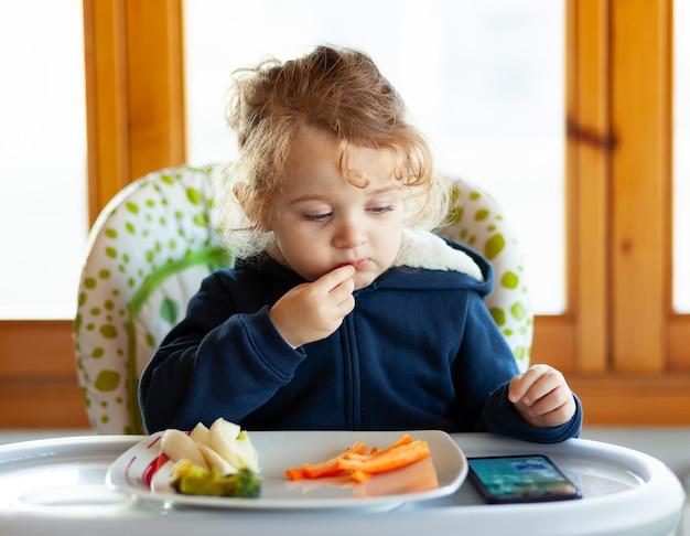El niño come mientras mira películas en el teléfono móvil. Foto Premium