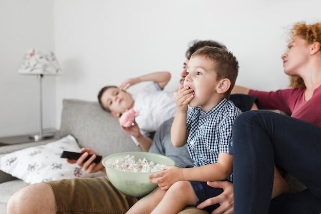 Niño comiendo palomitas mientras ve televisión con sus padres. Foto gratis