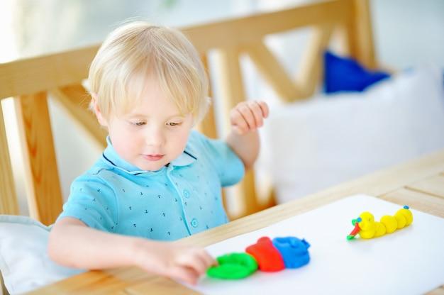 Niño creativo jugando con plastilina de colores en el jardín de infantes. Foto Premium