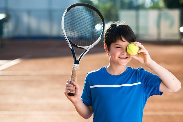Niño cubriendo su ojo con una pelota de tenis Foto Premium