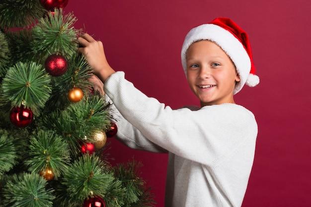 Niño Decorar árbol De Navidad Tiro Medio Foto Gratis