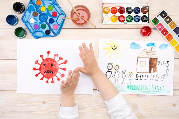 Un niño dibuja un coronovirus y su familia en una hoja de papel. Foto Premium