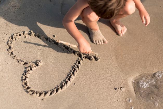 Niño dibujando un corazón en la arena Foto gratis