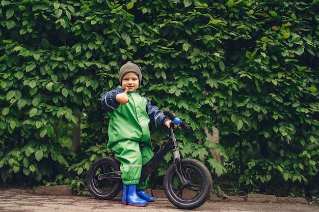 Niño divertido en botas de lluvia jugando en un parque de lluvia Foto gratis