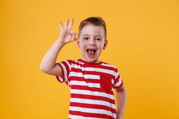 Niño emocionado de pie y mostrando gesto bien Foto gratis