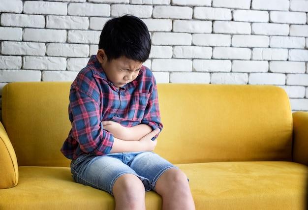 El niño estaba sentado en el sofá sintiendo dolor de estómago y estresado. Foto Premium