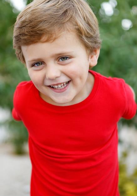 Niño feliz con camiseta roja en el jardín Foto Premium