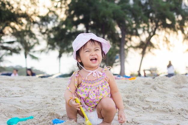 Niño feliz jugando con arena en la playa en verano Foto Premium