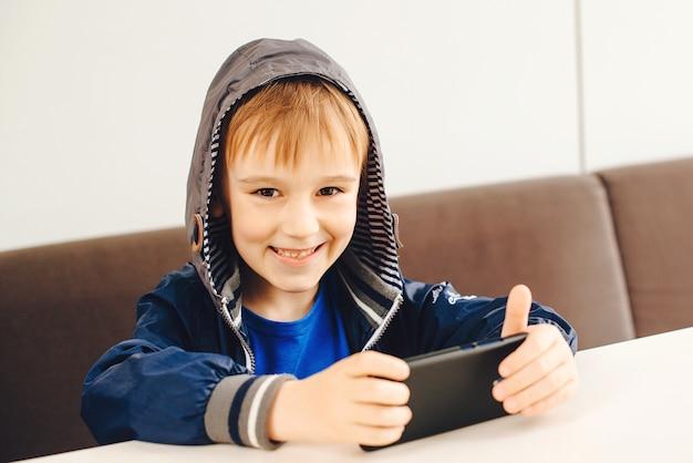 Niño feliz jugando en el teléfono móvil. niño viendo videos en el teléfono inteligente en la terraza exterior. Foto Premium