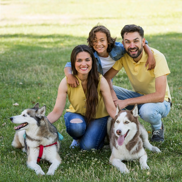 Niño feliz con perros y padres posando juntos en el parque Foto Premium