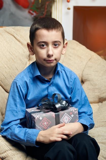 Niño feliz en una silla cómoda cerca del árbol junto a la chimenea recibió un regalo. Foto Premium