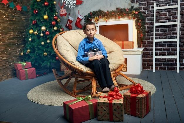 Niño feliz en una silla cómoda cerca del árbol de navidad junto a la chimenea con un montón de regalos. Foto Premium