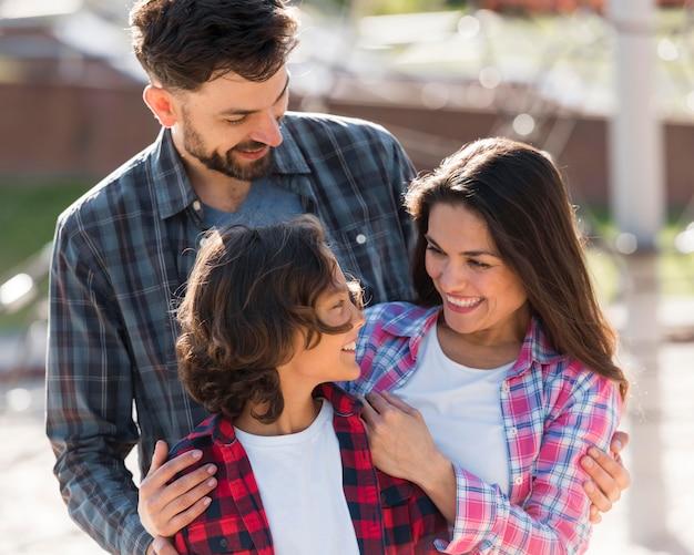 Niño feliz con sus padres disfrutando de su tiempo al aire libre Foto gratis