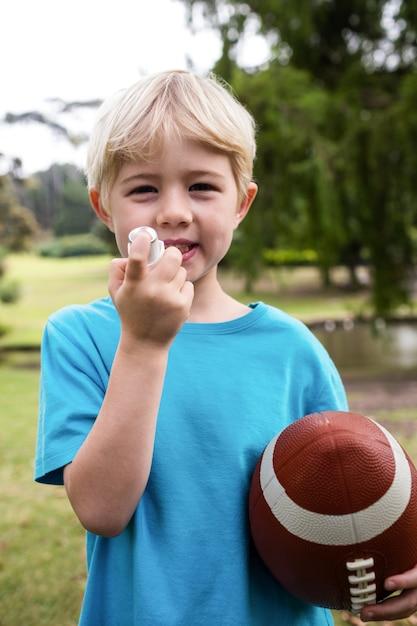 Niño con un fútbol americano usando un inhalador para el asma Foto Premium