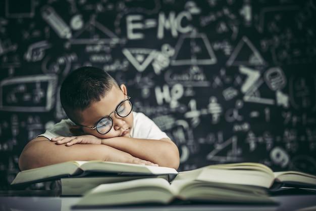Un niño con gafas estudiando y somnoliento. Foto gratis