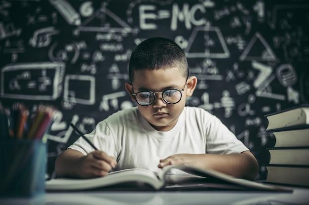 Un niño con gafas hombre escribiendo en el aula. Foto gratis