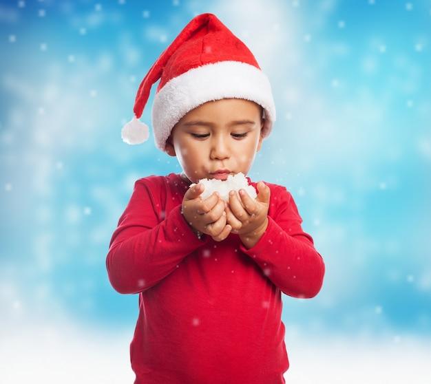 Niño con gorro de santa y soplando la nieve de sus manos  45ba30c8761