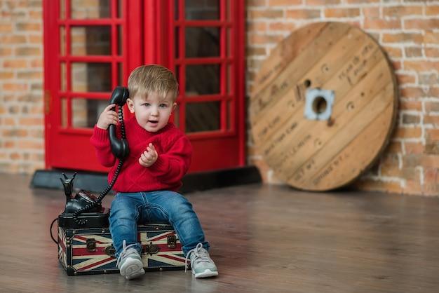 Un niño está hablando por teléfono cerca de una cabina telefónica roja en inglés Foto Premium