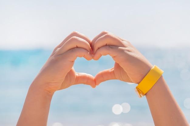 El niño hace un corazón con sus manos. Foto Premium