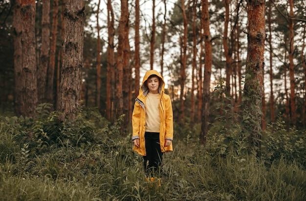 Niño en impermeable en el bosque de verano Foto Premium
