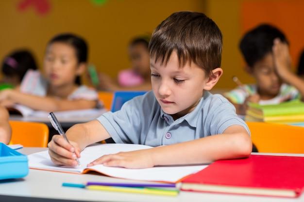 Niño inocente escribiendo en libro Foto Premium