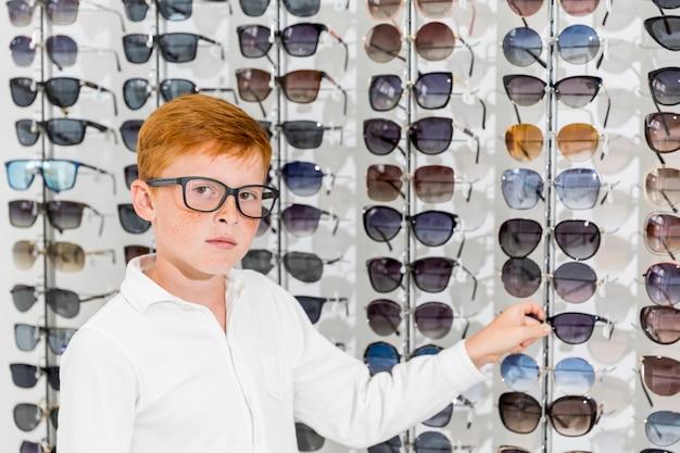 Niño inocente mirando a la cámara blanca con espectáculo en la tienda de óptica Foto gratis