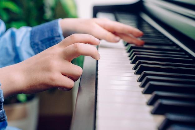 Niño irreconocible tocando el piano. detalle de las manos del niño pequeño tocando un teclado en casa. estudiante de músico pianista ensayando música clásica. estilo de vida musical educativo. Foto Premium