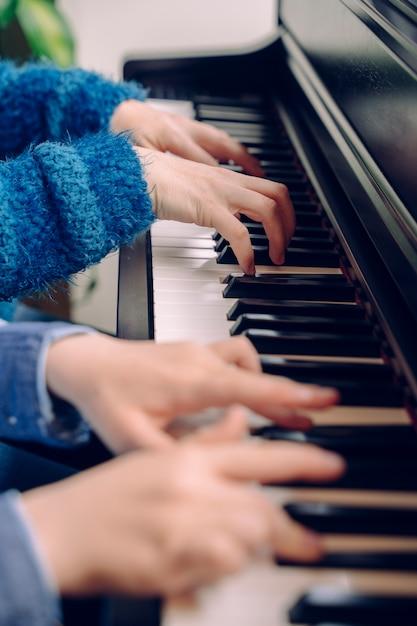 Niño irreconocible tocando el piano con el profesor de música. detalle de las manos del niño pequeño que tocan el teclado en casa. estudiante de músico pianista ensayando música clásica. estilo de vida musical educativo. Foto Premium