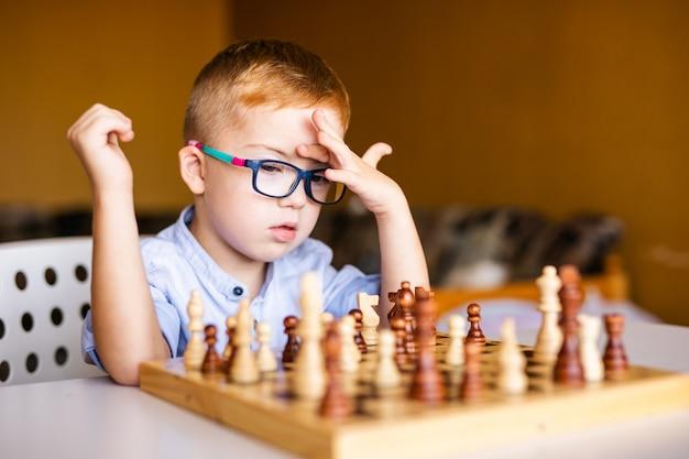 Niño jengibre con síndrome de down con anteojos grandes jugando ajedrez en casa Foto Premium