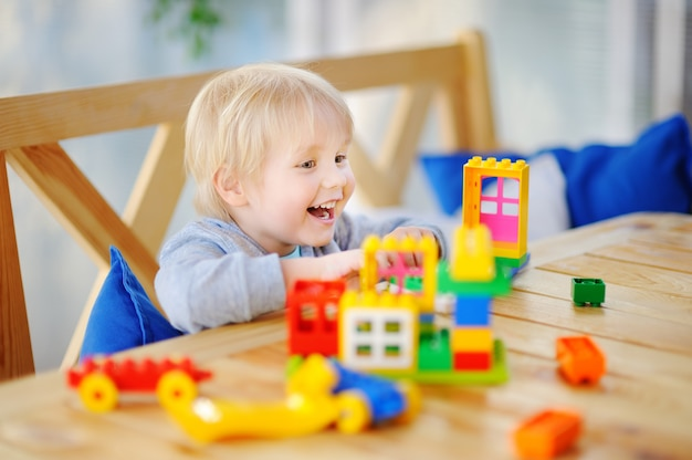Niño jugando con bloques de plástico de colores en el jardín de infantes o en casa Foto Premium