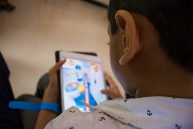 Un niño jugando un juego en su tableta Foto gratis