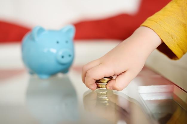 Niño jugando con monedas y sueños de lo que puede comprar. la educación de los niños en la educación financiera. Foto Premium