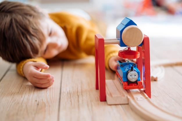 Niño jugando con tren de juguete Foto gratis