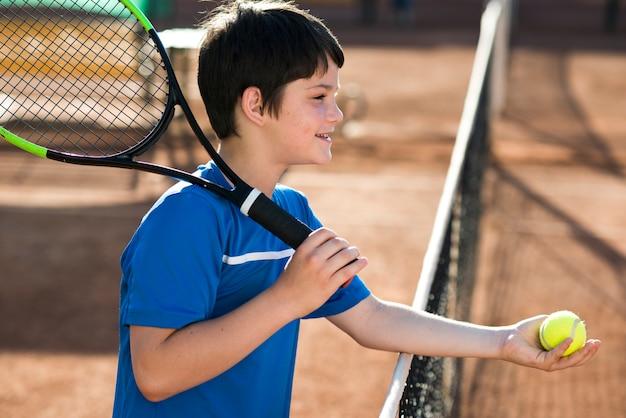 Niño de lado mostrando la pelota de tenis. Foto gratis