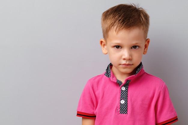 Niño lindo en camiseta rosa posando sobre fondo gris Foto Premium