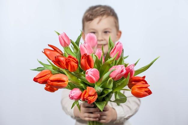 Niño lindo con un ramo de flores. tulipanes día de la madre. día internacional de la mujer. retrato de un niño feliz en una pared blanca. primavera. Foto Premium