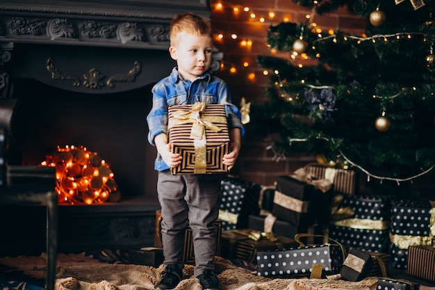 Niño lindo con regalo de navidad por árbol de navidad Foto gratis