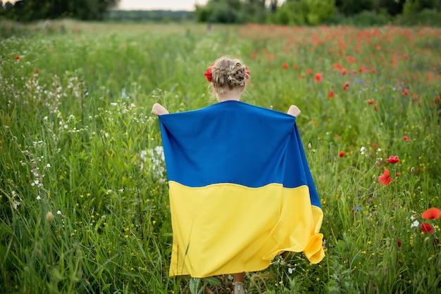 Niño lleva ondeando bandera azul y amarilla de ucrania en campo. día de la independencia de ucrania. día de la bandera. día de la constitución. chica en bordado tradicional con bandera de ucrania. Foto Premium