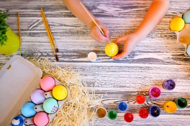 Niño manos pintando con colores blanco y amarillo huevos de pascua. familia preparándose para la pascua. manos de una niña con un huevo de pascua. de cerca Foto Premium