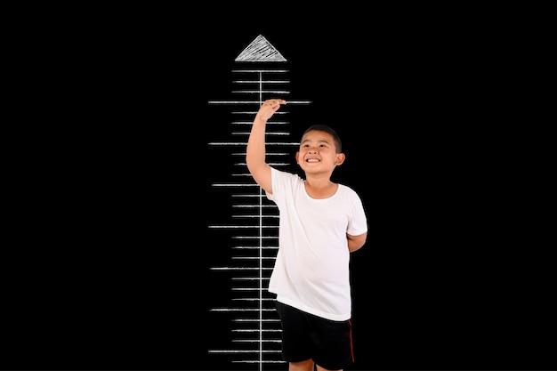 El niño midió la altura con el pizarrón. Foto gratis