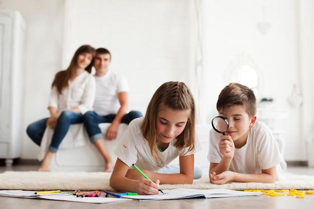 Niño mirando a través de la lupa durante su dibujo de la hermana en el libro frente a sus padres sentados sobre la cama Foto gratis
